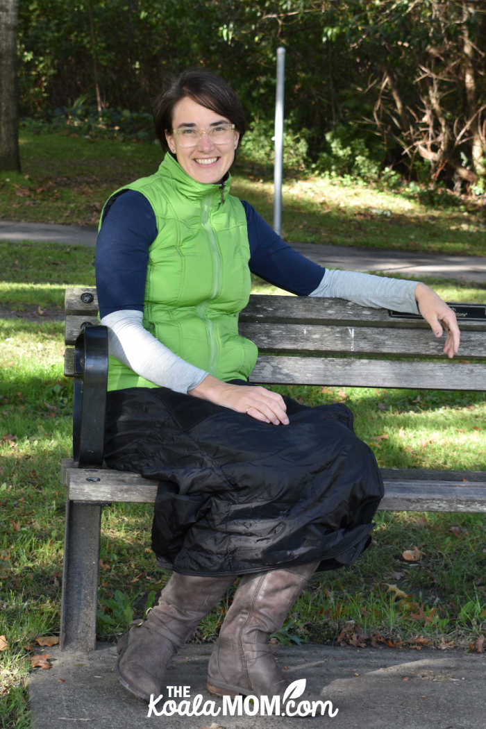 Happy woman on a park bench wearing a thermal wrap around her lower body to stay warm.