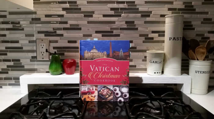 The Vatican Christmas cookbook, resting on a stove with salt and pepper shakers and three canisters labeled garlic, pasta and utensils.