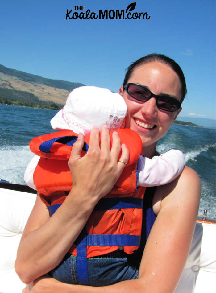 Mom holding her toddler in a PFD while riding in a motor boat.