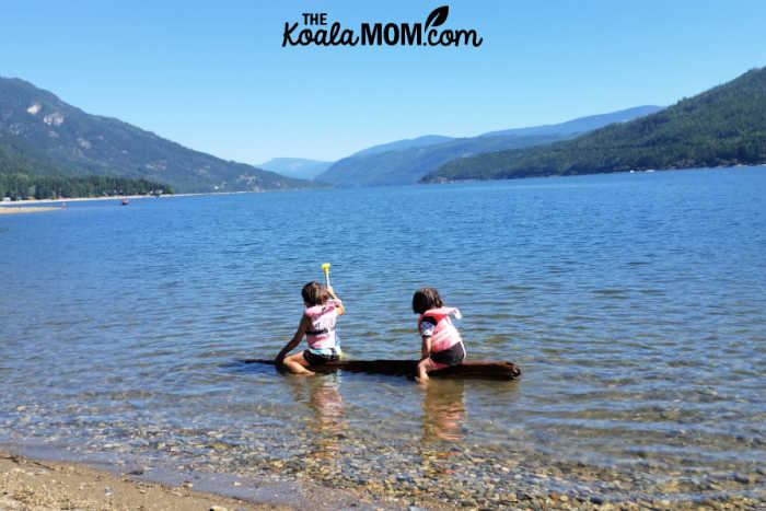 Kids wearing their PFDs and playing in a lake with a floating log.