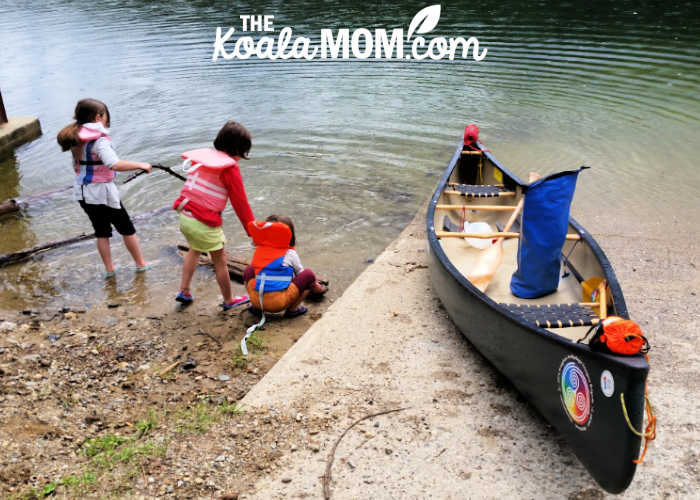 Three girls wearing their PFDs playing beside a canoe on a boat launch.