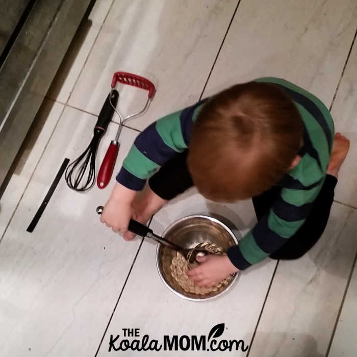 Toddler whipping up a batch of cheerios and rice krispies in the kitchen.