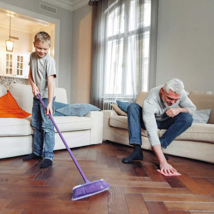 Father and son cleaning a clutter-free living room together.