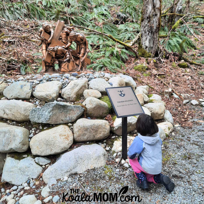 Five-year-old kneels at the third Station of the Cross at Little Carmel Monastery.