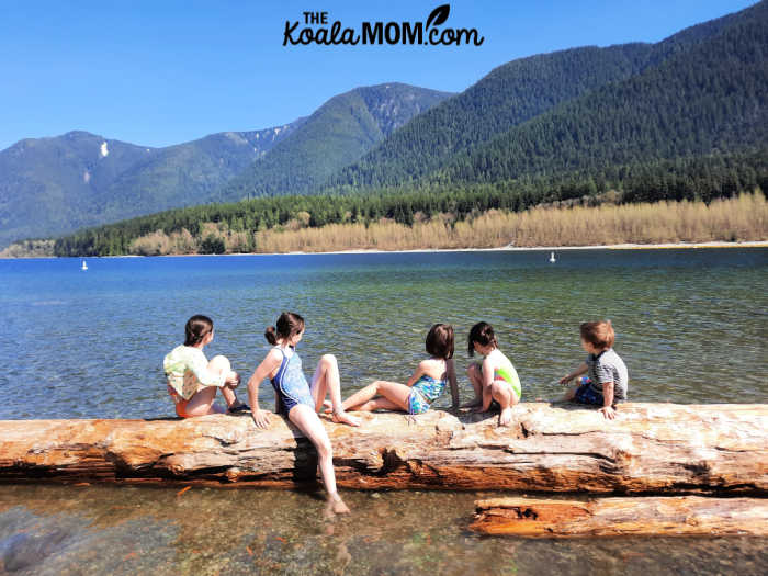 Five kids sitting on a log in Alouette Lake.