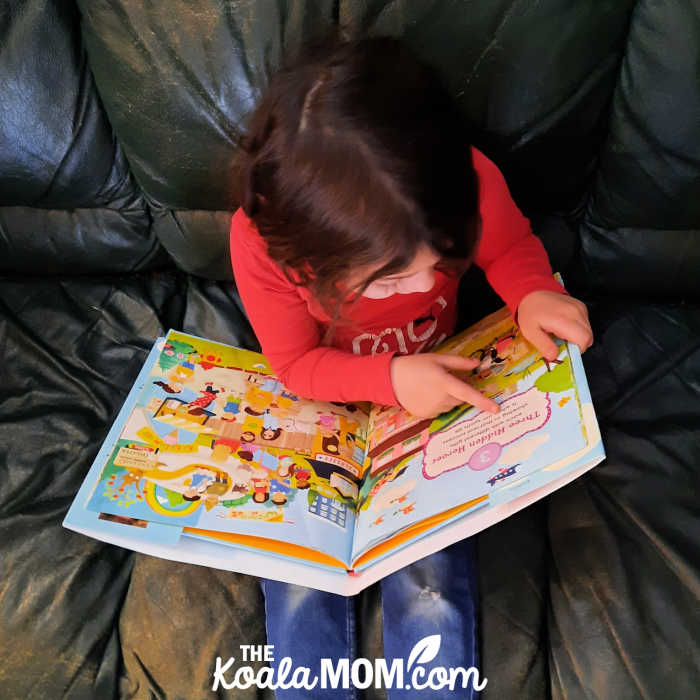 5-year-old looks at a seek and find counting book.