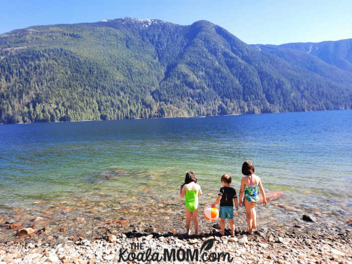 Three kids stand on the edge of Alouette Lake in Golden Ears Provincial Park.