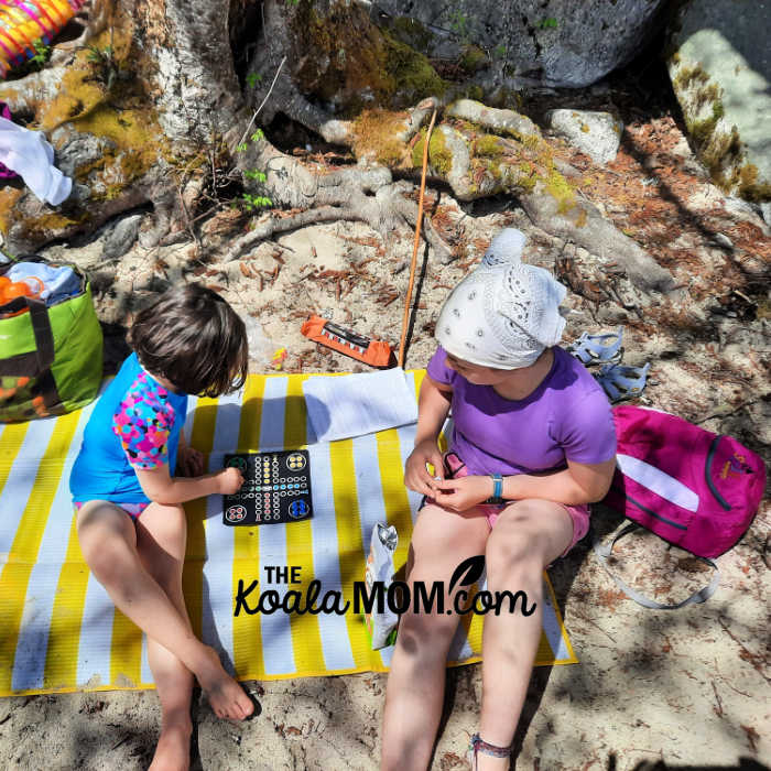 Two sisters play a magnetic board game on a beach.