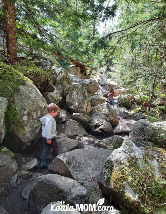 A 5-year-old and a 3-year-old pick their way over the trail through the boulder field on the Lindemann Lake Trail.