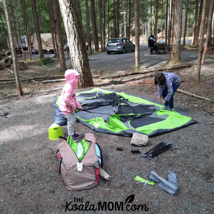10-year-old and 8-year-old help take down the tent.