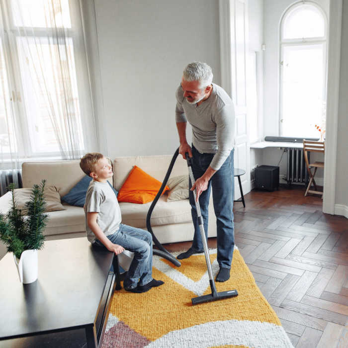 Dad vacuuming the living room while chatting with his son.