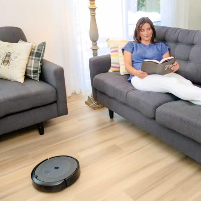 Mom reading while a robot vacuum cleans her hardwood floor.