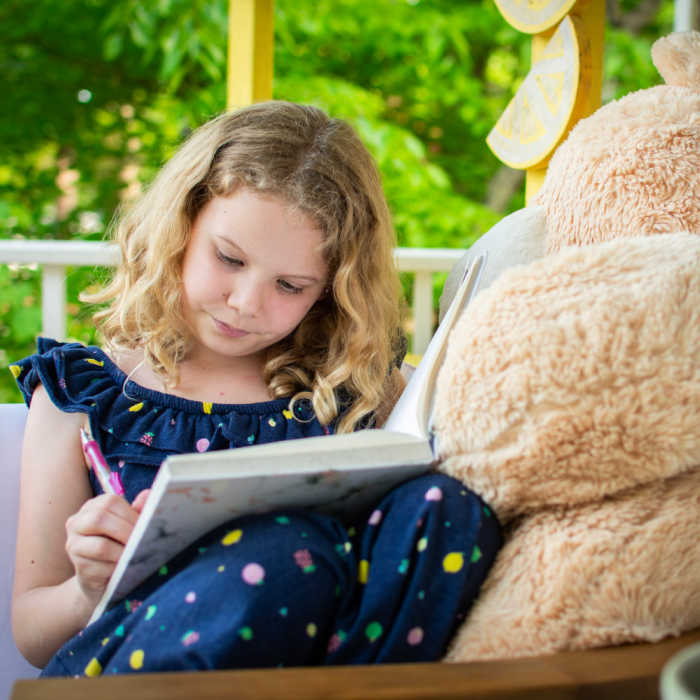 A young girl writes in her diary while sitting beside her giant stuffed teddy bear.