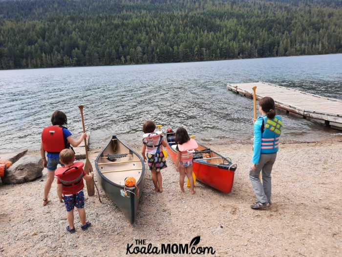 Five kids in life jackets beside two canoes, ready to paddle on Clearwater Lake.