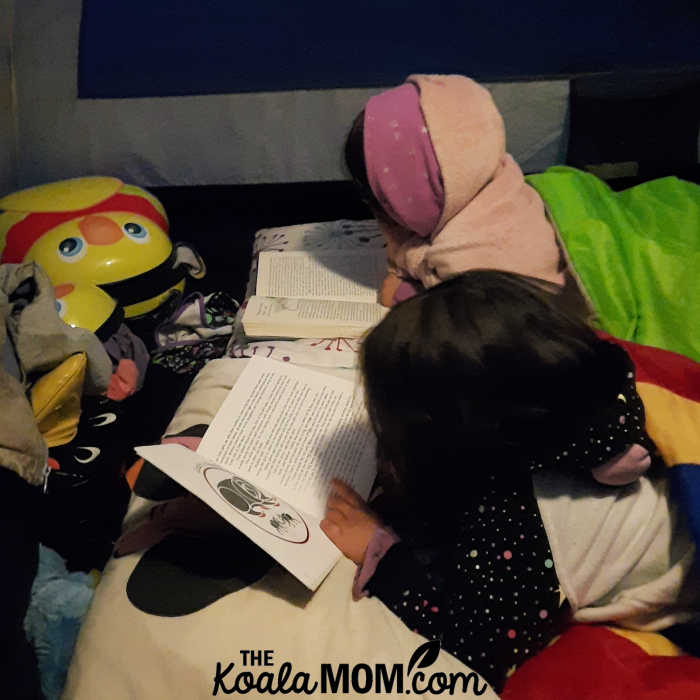 An 8-year-old and 5-year-old read their books in the tent.