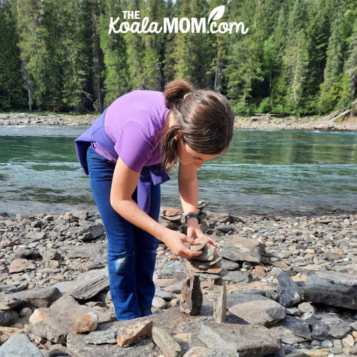 Teenager stacking stones on a beach in Wells Gray Provincial Park.